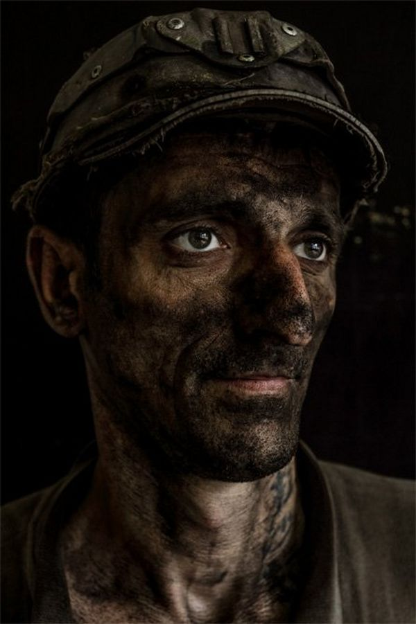 A portrait of a miner looking to his left, with a solemn look and black coal dust covering his face.