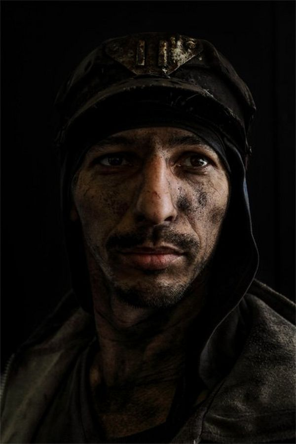 A portrait of a miner with only half his face illuminated