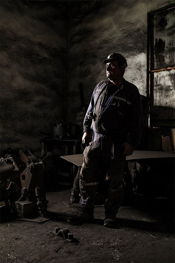 Environental portrait of a miner in a decaying, dust-covered industrial setting.
