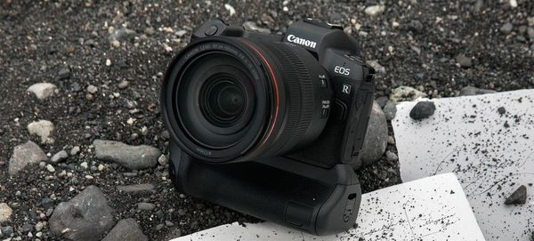 The Canon EOS R sits on a pile of black stones, some dirty paper underneath it