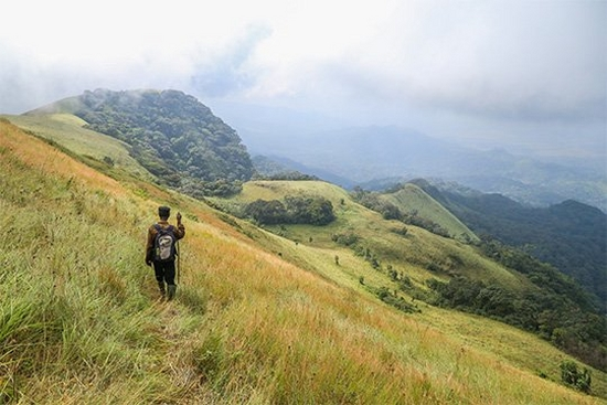 A walker on a grassy mountain slope, photographed by Daniël Nelson on a Canon EOS 6D.