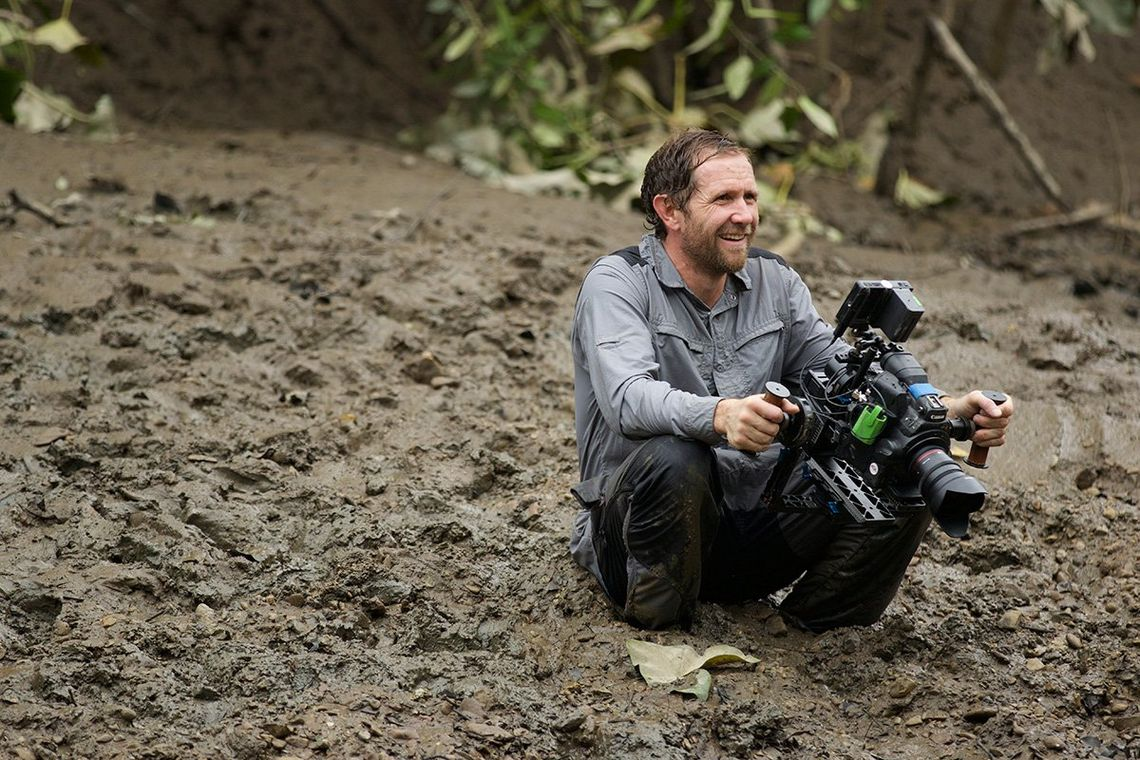 A rain-soaked but smiling Danny sits in several inches of mud holding a camera in both hands.