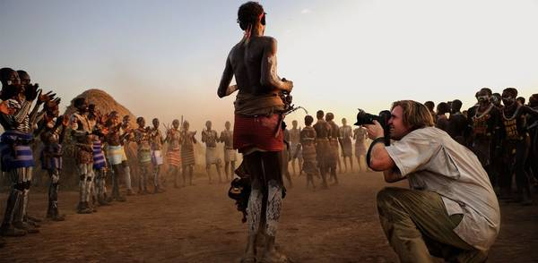 A photojournalist crouches beside a man in tribal African dress to take his photograph, while others dressed in traditional tribal clothes clap and dance.