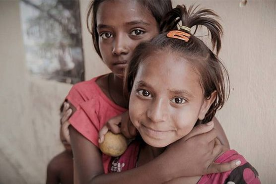 Two girls embrace each other in Kolkata, during the making of McCullin in Kolkata for Canon Europe.
