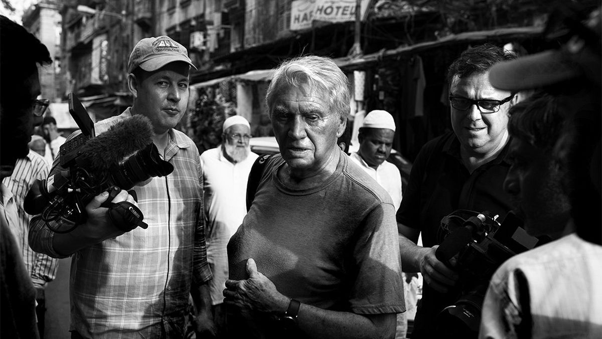 Sir Don McCullin stands, camera in hand, in the middle of a crowd in Kolkata.