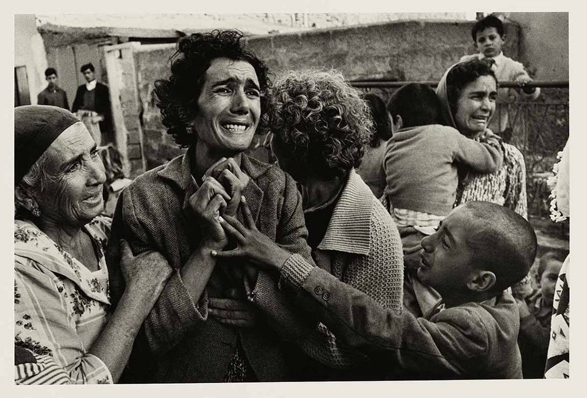 A grieving Turkish woman is comforted by others and clutches her hands to her chest as she mourns her husband, a victim of the Cyprus Civil War.
