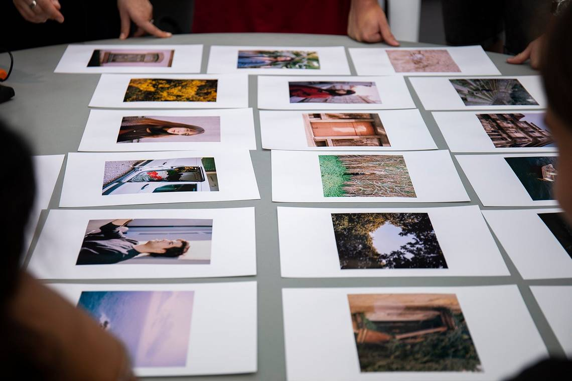 Photos are laid out on a table to be reviewed.