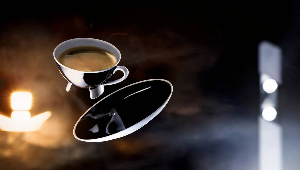 A metal cup of coffee and saucer appear to float in the air. Photo by Eberhard Schuy