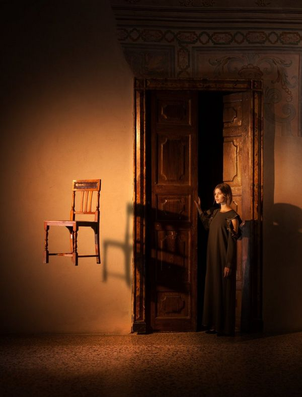 A woman stands by a wooden door, while a chair appears to be suspended in the air. Photo by Eberhard Schuy