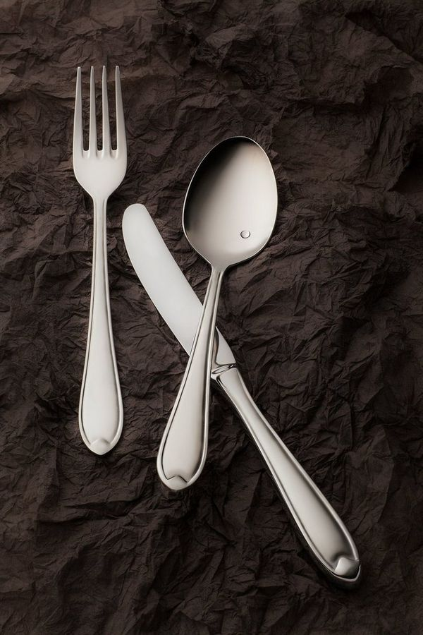 A close-up of a fork, knife and spoon on a dark background. Photo by Eberhard Schuy