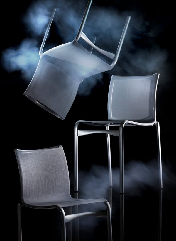 Three chairs, one seemingly suspended upside down, against a black background and with smoke effects. Photo by Eberhard Schuy