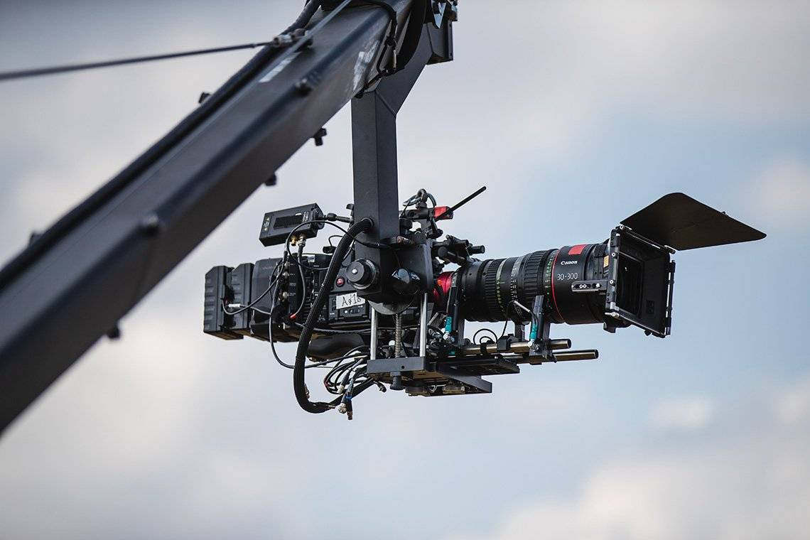 A Canon EOS C700 FF in front of a blue sky hanging from a camera crane.
