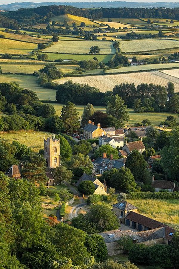 The tower of the church and surrounding houses nestle among greenery in the village of Corton Denham in Somerset, England.