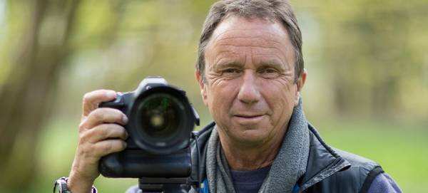 David Noton with a Canon DSLR as he stands in a woodland.