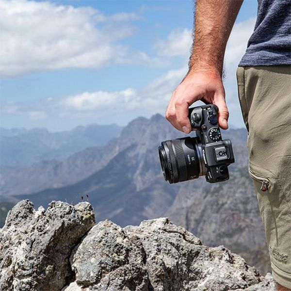 A photographer holds a Canon EOS RP up a mountain.