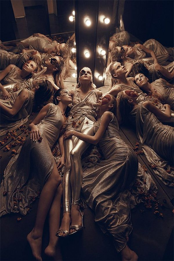 Female models wearing gold lie together in a dimly lit space with mirrors. Photo by Jaroslav Monchak on a Canon EOS 5DS R with Canon EF 24-70mm f/2.8L II USM lens.