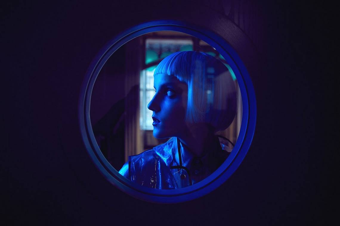 A profile of a woman behind a circular window, shot with a blue gel filter. Taken by Jaroslav Monchak.
