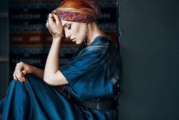 A woman in a dark blue silk dress and a patterned headscarf sits with her back against a wall and her forehead resting in her hand. Taken by Jaroslav Monchak.