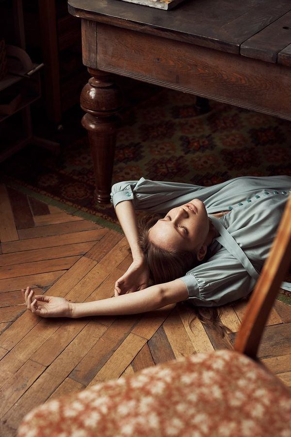 A woman lies underneath a table with her arms above her head. Taken by Jaroslav Monchak.