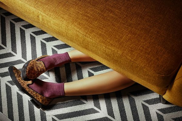 A pair of feet, in purple socks and animal-print loafers, poking out from underneath a mustard velvet sofa. Taken by Jaroslav Monchak.