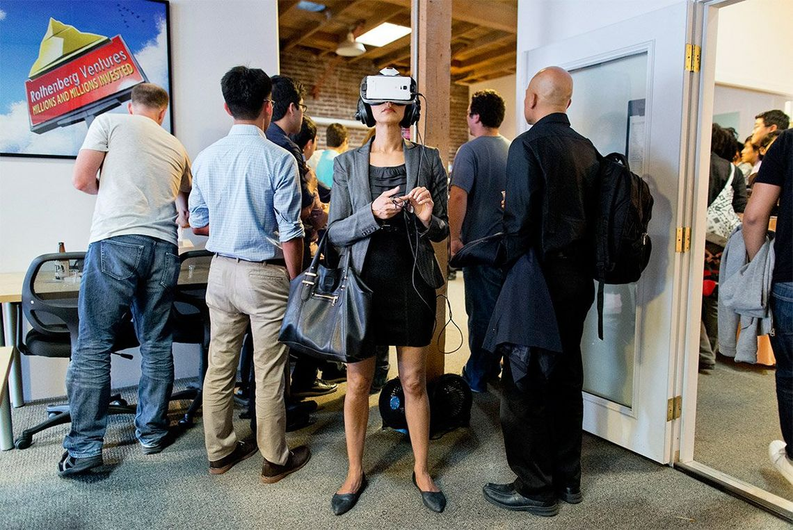 A well-dressed young woman with a large handbag stands facing the camera wearing a VR headset and earphones, completely absorbed, while everyone else in the room is facing the opposite direction.