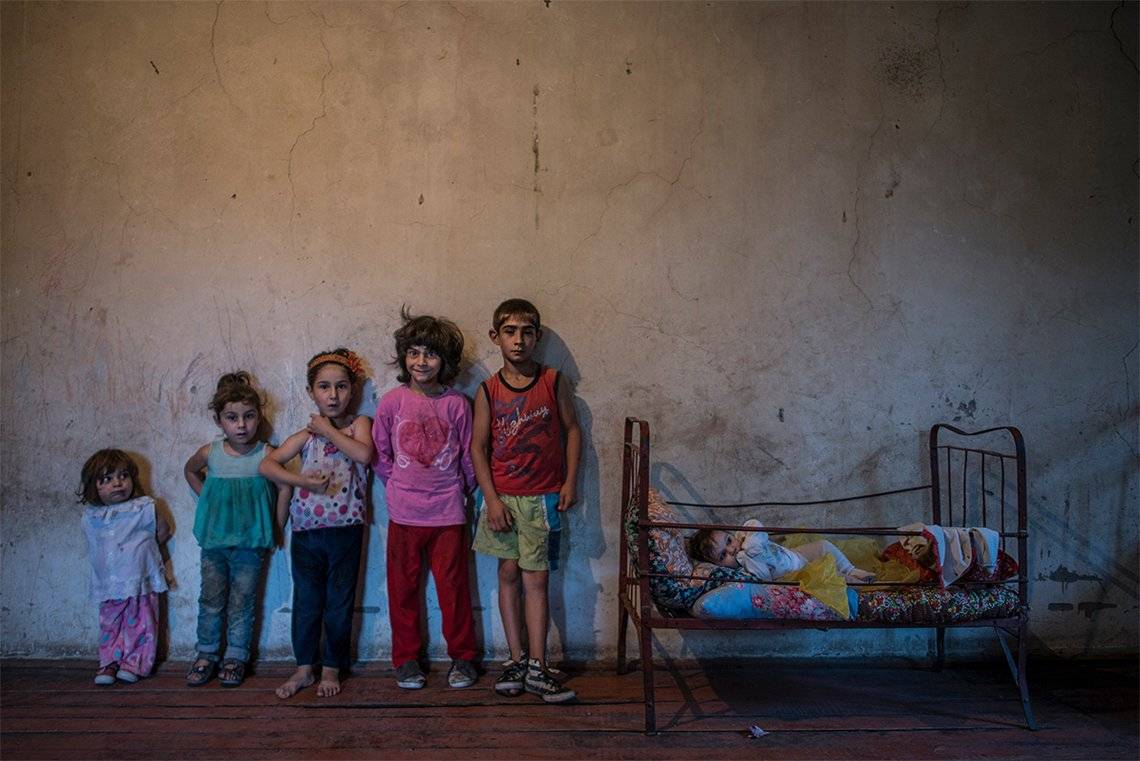 Six siblings pose for a portrait against a bare wall in a sparsely-furnished room. Photo by Anush Babajanyan