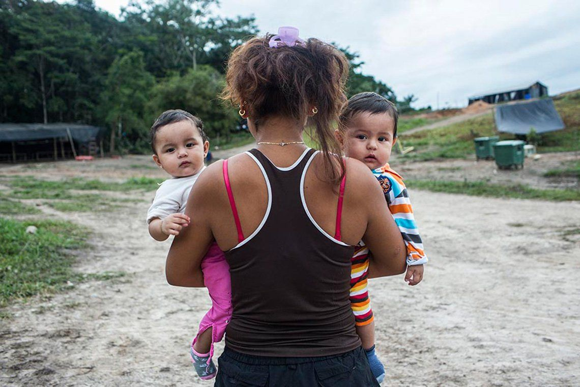 A female ex-member of Columbian militant group FARC stands with her back to the camera, holding two infant children in her arms who look into the camera.