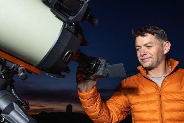Fergus Kennedy holds a Canon EOS Ra to a large telescope, the tilt screen angled upwards.