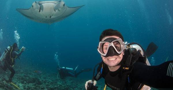 Fergus Kennedy is underwater in goggles and diving gear, though he has removed his breathing mask to smile for the camera. Behind him is a manta ray and two other divers.