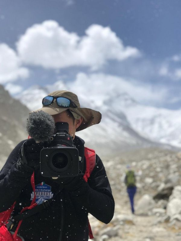 Filmmaker Sam Tongue holds a Canon EOS C200 video camera in front of Mount Everest.