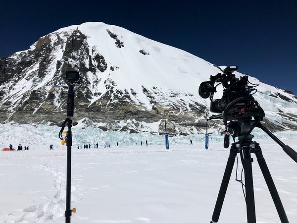 A Canon EOS C200 camera set up on a tripod to film a rugby match in the shadow of a snow-covered mountain.