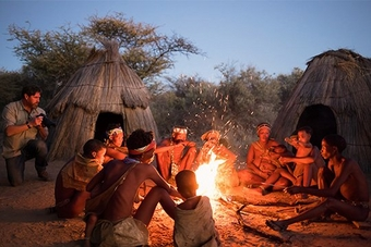 Brent Stirton photographs Namibian tribespeople by the fire, as Spencer MacDonald films him using a Canon EOS C200.