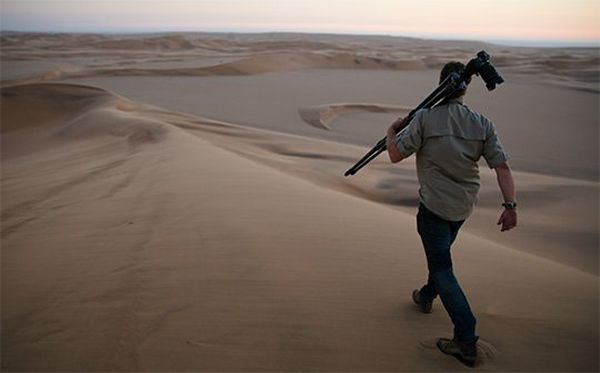 Brent Stirton strides across the desert at dusk with his camera, as Spencer MacDonald films him using a Canon EOS C200.