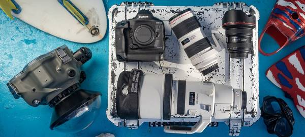 A Canon EOS-1D X Mark III and lenses on a well-used hard case with an underwater camera housing, flippers and other kit.
