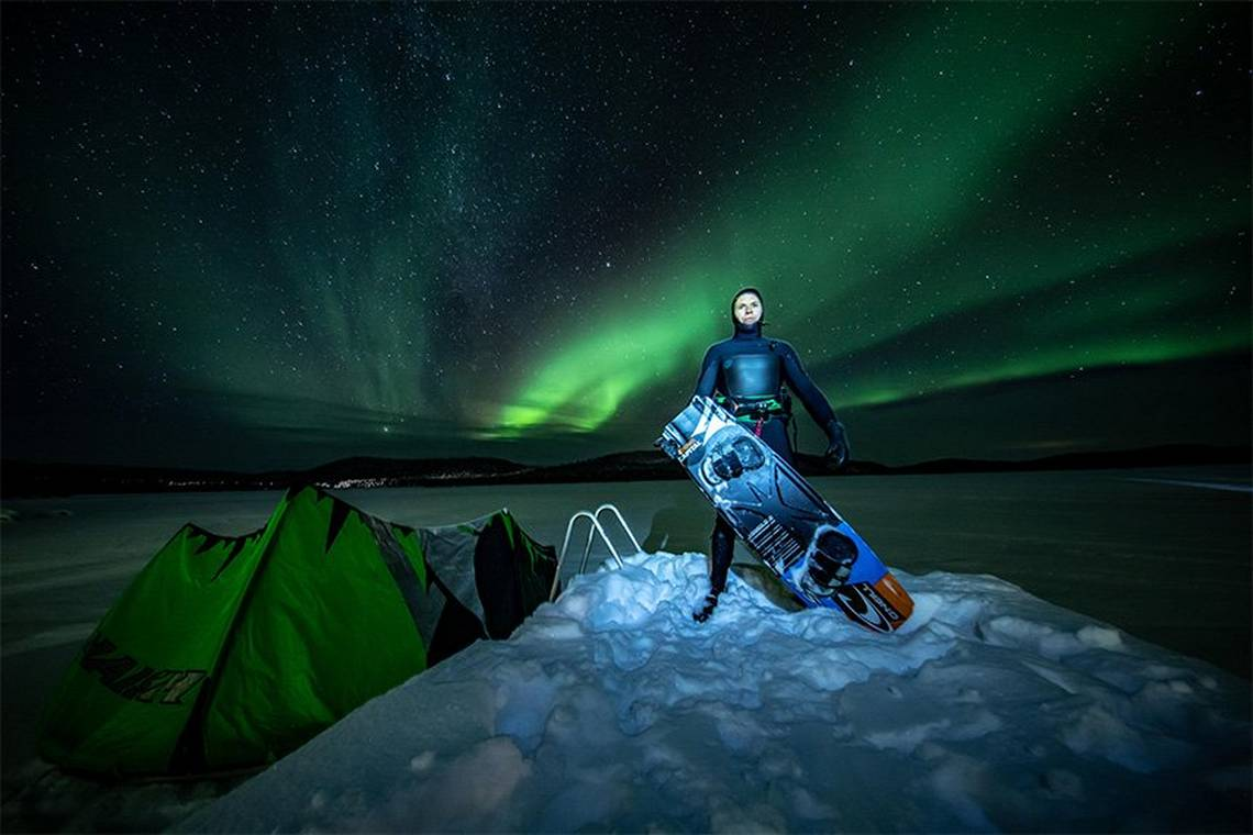 Professional kite surfer Kevin Langeree with his board in front of an Aurora Borealis-filled sky. Photo by Humberto Tan.