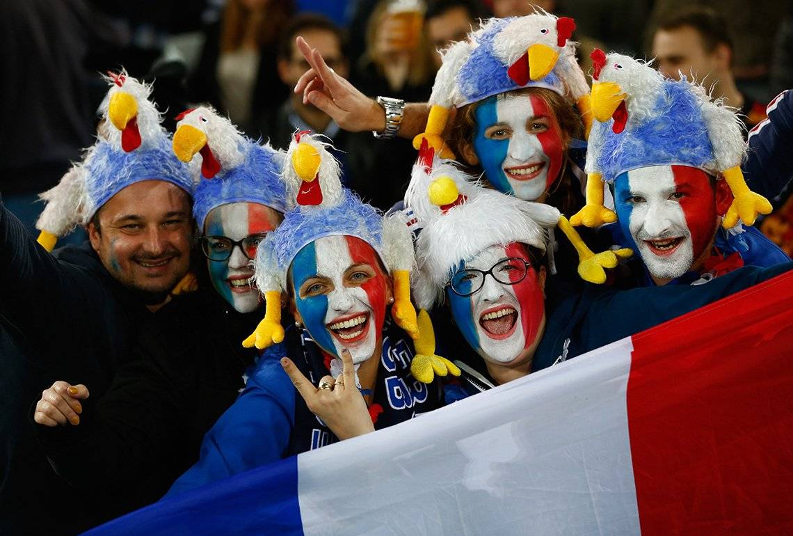 French fans with painted faces holding a flag at a France v Romania match in Rugby World Cup 2015.