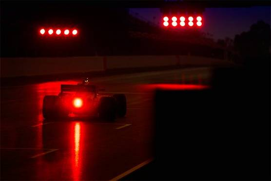 A low-light photo from the rear of the racing car driven by Fernando Alonso, its brake lights emitting a red glow on the wet track.
