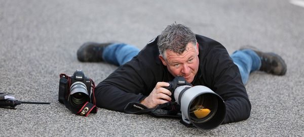 Sports photographer Frits van Eldik lying prone on a racetrack with a Canon EOS-1D X Mark II camera and telephoto lens.