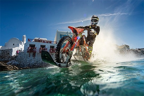 A driver on a customised dirt bike, riding it on the water.