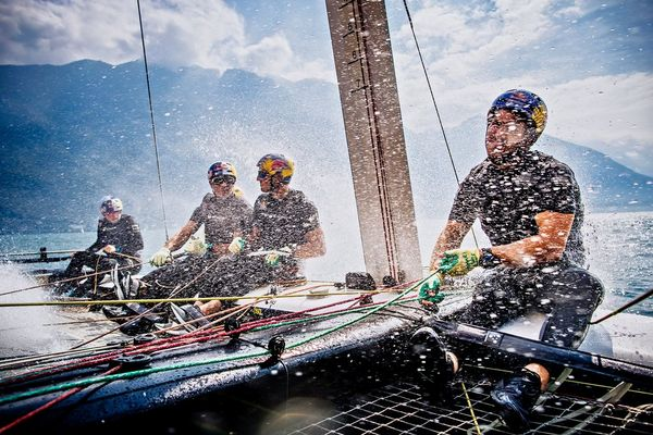 Four men on a racing catamaran bracing against the spray from the sea.