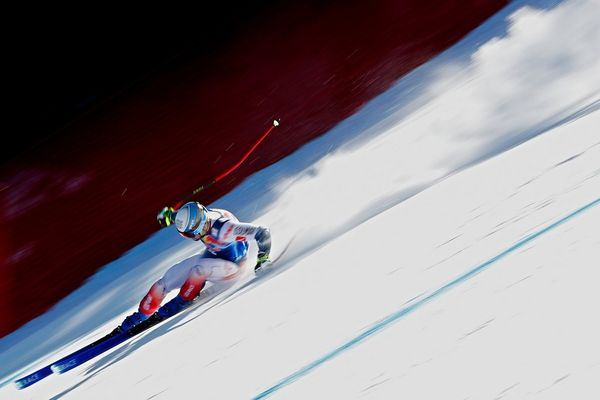 A skier performing a turn on a steep downhill run.