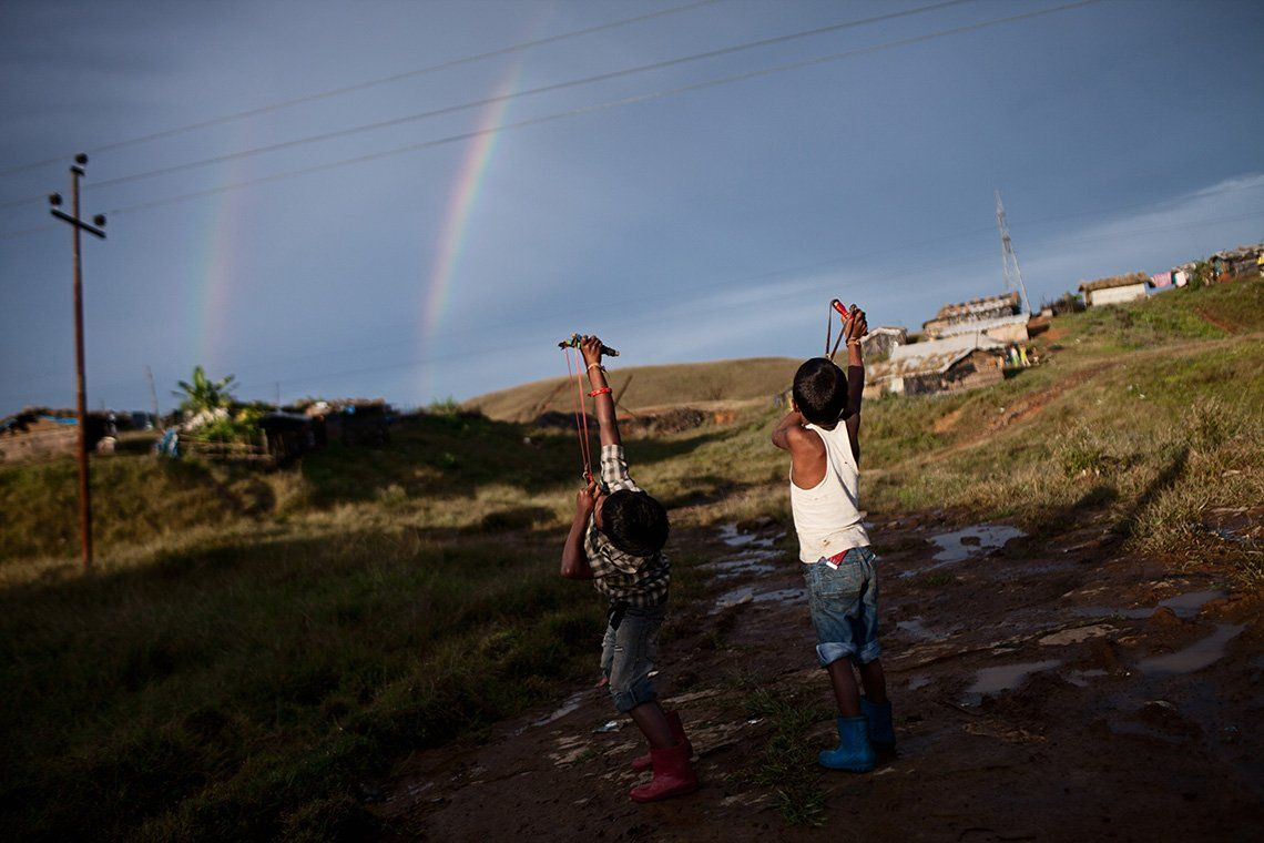 Two boys direct their slingshots to a sky filled with a double rainbow and telephone cables.