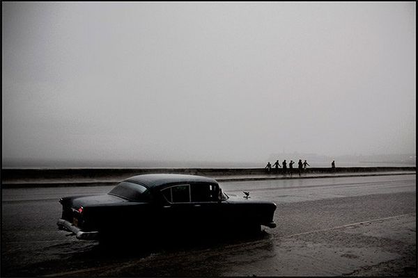 An old car drives through a large puddle in the rain on Havana's seafront road, the Malecon.