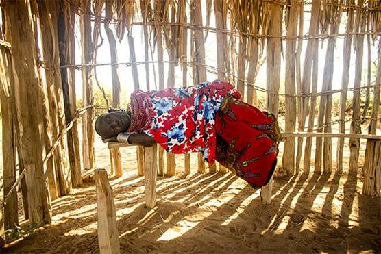 A woman sleeps on a narrow bench in a wooden hut in the all-female Umoja village in northern Kenya.