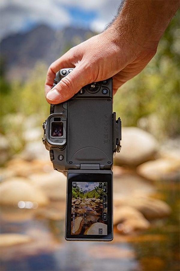 A man holds a Canon EOS RP by a stream.