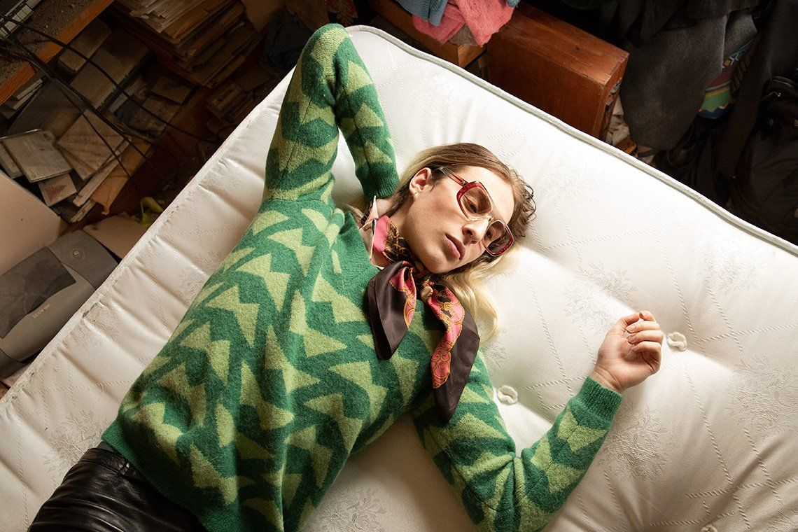 An androgynous long-haired model wearing a striped top and scarp lies on a bed. Photo by Wanda Martin on a Canon EOS-1D X Mark II.