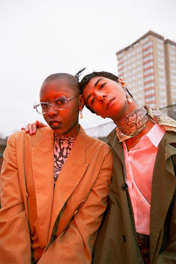 A male and female model pose outside a block of flats, an orange glow on them. Photo by Rianna Gayle on a Canon EOS-1D X Mark II.