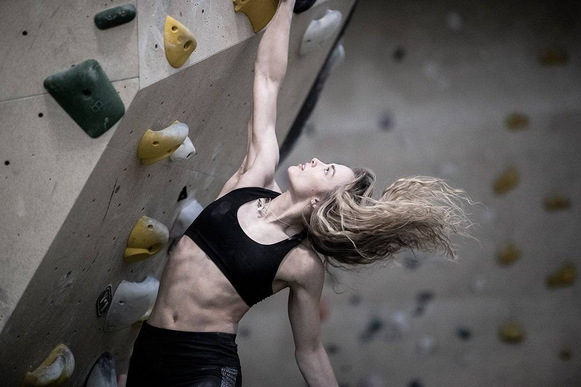 Climber Imogen Horrocks hangs from a climbing wall by one hand. Photo by Julian Finney.