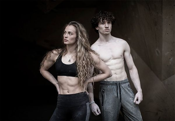 A female climber stands with hands on hips, with a male climber behind her.