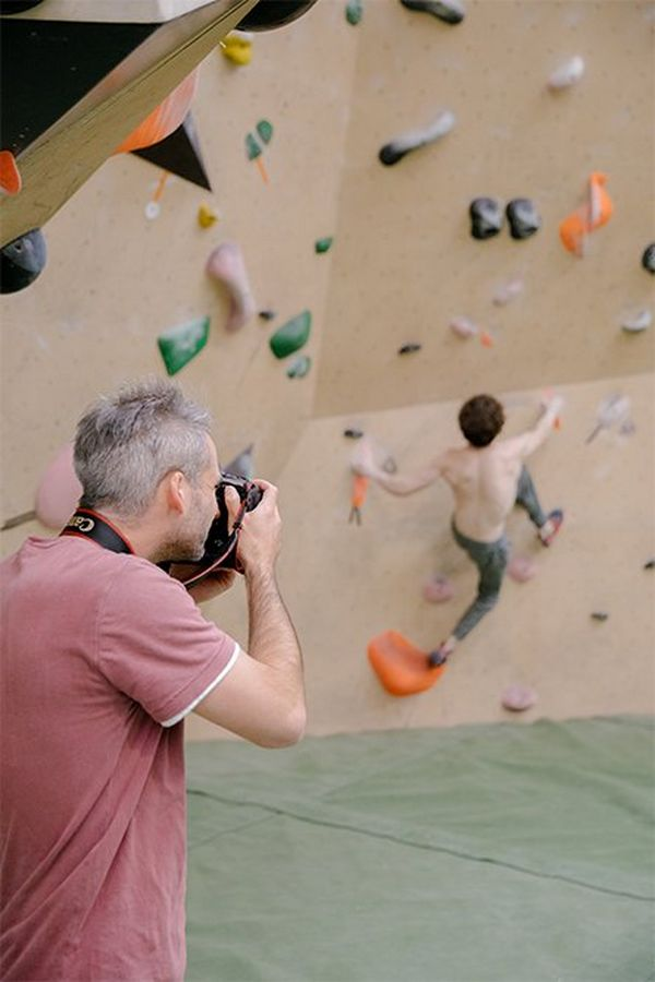 Julian Finney photographs climber Declan Rounthwaite beginning to scale a wall without a rope or harness.